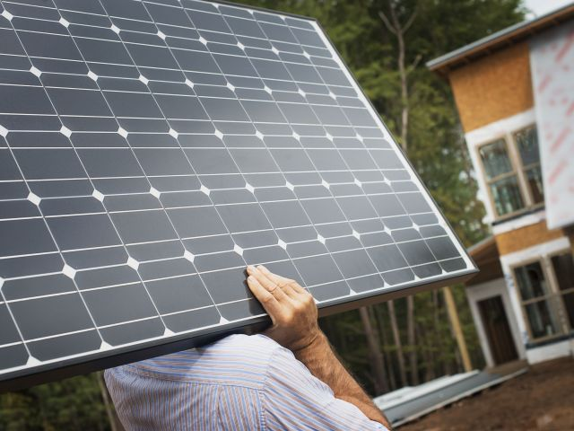 Solar Panel at Green Construction Site,USA,A workman carrying a large solar panel at a green house construction site.