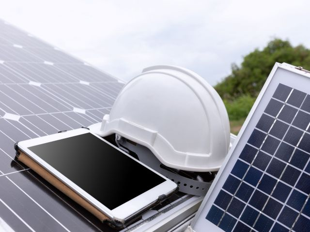 Engineer solar photovoltaic panels station checks with tablet co