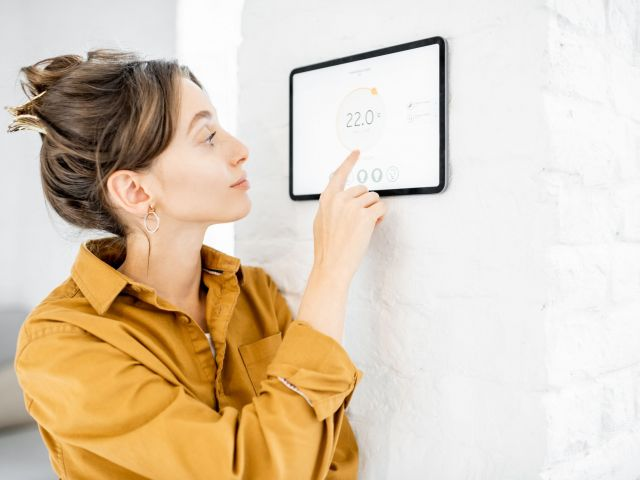 Woman controlling room temperature with a digital touch screen panel